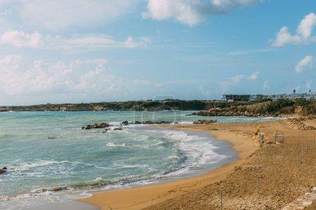 Photo pour Littoral et plage de sable près de la mer Méditerranée contre ciel bleu - image libre de droit