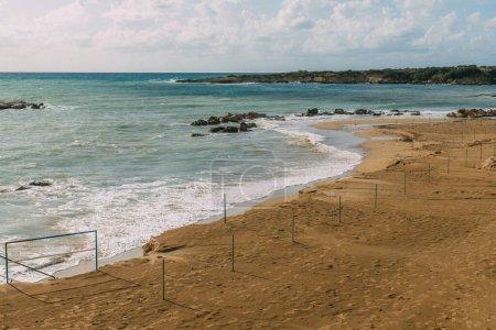 wet sandy beach near mediterranean sea against blue sky