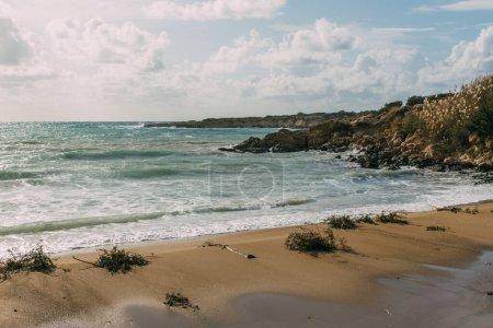 wet and sandy beach near mediterranean sea against blue sky