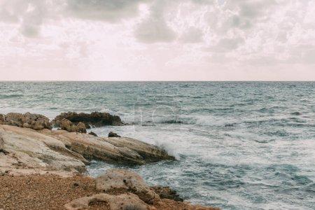 Photo pour Littoral avec des pierres près de la mer Méditerranée contre le ciel avec des nuages - image libre de droit