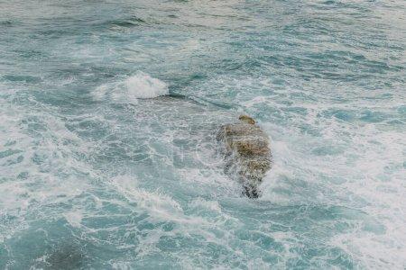 Photo pour Mousse blanche près de la roche dans l'eau bleue de la mer Méditerranée - image libre de droit