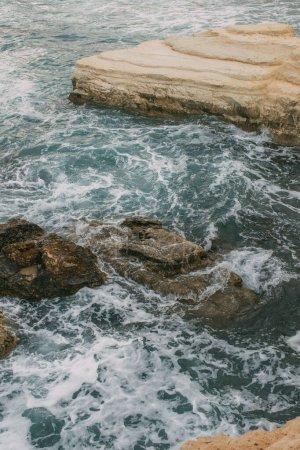Photo pour Mousse blanche près des rochers dans l'eau bleue de la mer Méditerranée - image libre de droit
