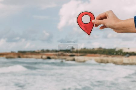 Photo for Cropped view of woman holding red location paper near coastline of mediterranean sea in cyprus - Royalty Free Image