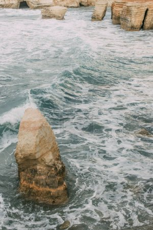 Photo for White foam near wet stones in water of mediterranean sea in cyprus - Royalty Free Image