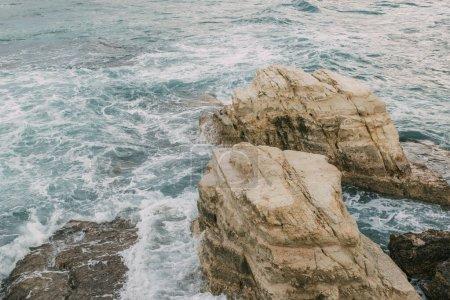 Photo pour Mousse blanche près des roches humides dans l'eau de la mer Méditerranée à Cyprus - image libre de droit