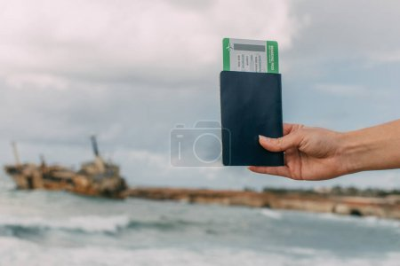 Photo for Cropped view of traveler holding passport and boarding pass near mediterranean sea - Royalty Free Image