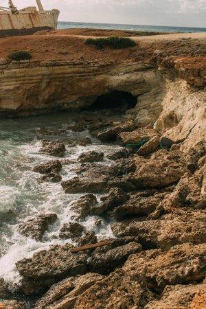 Foto de Rocas húmedas cerca del mar Mediterráneo contra el cielo con nubes blancas. - Imagen libre de derechos