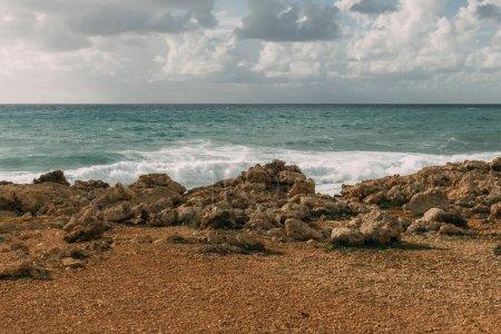 Photo pour La lumière du soleil sur les rochers près de la mer méditerranéenne contre ciel avec des nuages blancs - image libre de droit