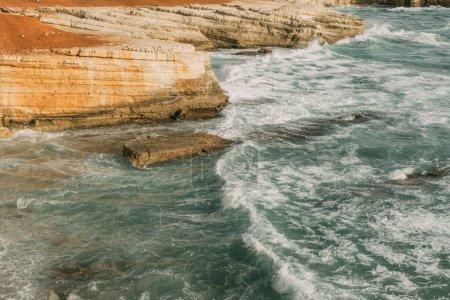 Photo pour Mousse blanche près des rochers en mer bleue - image libre de droit