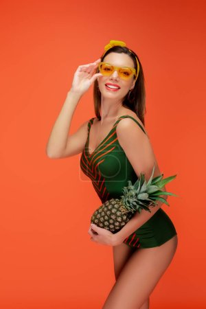 Photo for Woman in sunglasses holding pineapple smiling and looking at camera isolated on orange - Royalty Free Image