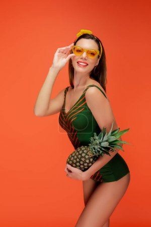 Photo pour Femme aux lunettes de soleil tenant l'ananas souriant et regardant la caméra isolée sur orange - image libre de droit