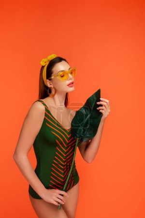Photo for Woman in swimsuit and sunglasses looking at green leaf isolated on orange - Royalty Free Image