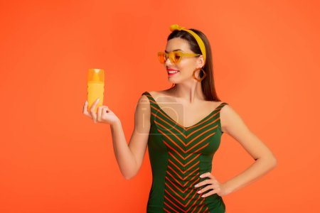 Photo for Front view of woman with hand on hip looking at bottle of sunscreen and smiling isolated on orange - Royalty Free Image