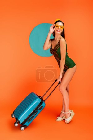 Photo for Girl holding suitcase, smiling, looking at camera and touching sunglasses with blue circle behind on orange background - Royalty Free Image