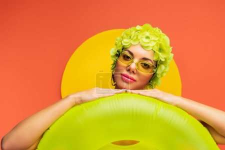 Portrait of girl in hat with decorative flowers and sunglasses putting hands on swim ring on yellow and orange