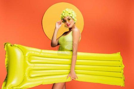 Photo pour Fille en chapeau avec des fleurs décoratives souriant, touchant des lunettes de soleil et tenant un matelas gonflable avec un cercle jaune derrière sur orange - image libre de droit