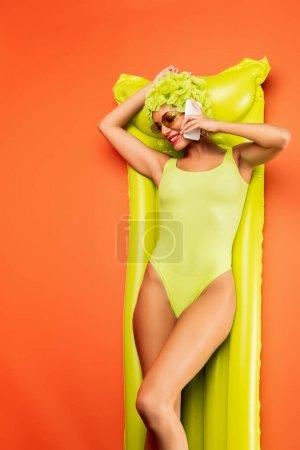 Photo pour Vue du dessus de la femme souriante, reposant sur un matelas gonflable et parlant sur un smartphone sur fond orange - image libre de droit