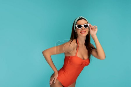 Photo for Woman with hand on hip touching sunglasses and smiling isolated on blue - Royalty Free Image