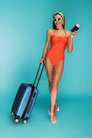 Foto de Hermosa mujer con maleta, pasaporte y billete de avión sonriendo sobre fondo azul - Imagen libre de derechos