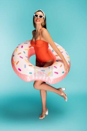Photo pour Femme avec anneau gonflable soulevant la jambe et souriant sur fond bleu - image libre de droit