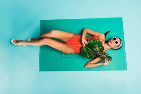 Photo pour Vue du dessus de la femme aux feuilles vertes couchée sur la couverture de plage sur bleu - image libre de droit