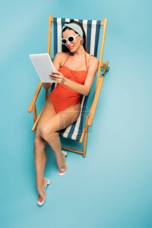 Photo for High angle view of woman with digital tablet smiling on deckchair on blue - Royalty Free Image