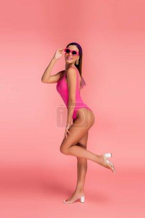 Photo pour Vue latérale de la femme souriante, touchant les lunettes de soleil et soulevant la jambe sur rose - image libre de droit