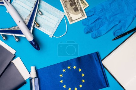 Photo for Top view of toy plane, medical mask with hand sanitizer and flag of european union on blue background - Royalty Free Image