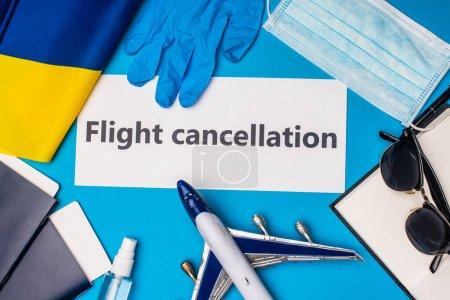 Photo pour Vue du dessus de la carte avec lettrage d'annulation de vol près du masque médical, passeports avec billets d'avion et drapeau de l'Ukraine sur fond bleu - image libre de droit
