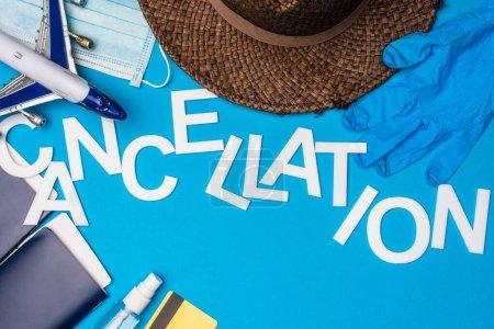 Photo pour Haut de la page Annulation de lettres près d'un avion-jouet, d'un masque médical et de passeports avec billets d'avion sur fond bleu - image libre de droit