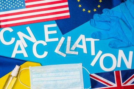 Photo pour Vue du dessus de l'annulation de lettrage près du masque médical, gants en latex et drapeaux des pays sur la surface bleue - image libre de droit