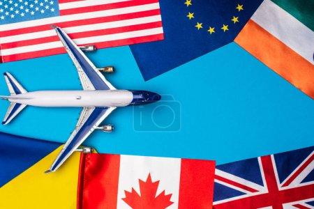 Photo pour Vue du dessus de l'avion jouet près des drapeaux des pays sur fond bleu - image libre de droit