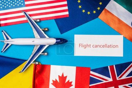 Photo pour Vue du dessus de l'avion jouet près de la carte avec lettrage d'annulation de vol et drapeaux des pays sur la surface bleue - image libre de droit