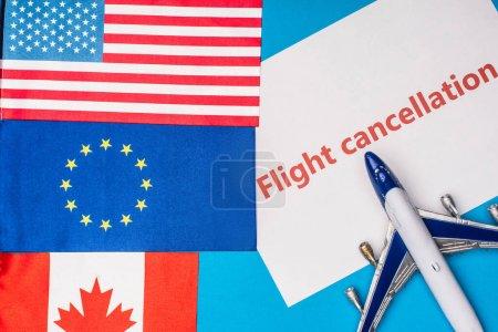 Photo pour Vue du dessus des drapeaux du canada, de l'union européenne et de l'Amérique près de l'avion jouet avec inscription d'annulation de vol sur la carte sur la surface bleue - image libre de droit