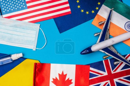 Photo for Top view of toy plane near medical mask and flags of countries on blue background - Royalty Free Image