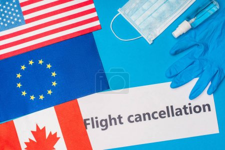 Photo for Top view of card with flight cancellation lettering near medical mask and flags of countries on blue surface - Royalty Free Image