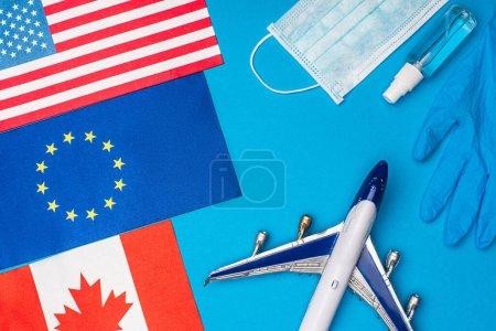 Photo pour Vue du dessus de l'avion jouet, bouteille avec désinfectant pour les mains près des drapeaux des pays sur fond bleu - image libre de droit