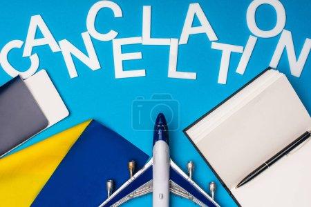 Photo pour Vue du dessus du lettrage d'annulation près de l'avion jouet, passeport avec billet d'avion et drapeau de l'ukraine sur fond bleu - image libre de droit
