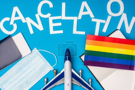 Photo for Top view of toy plane, passport near medical mask with lgbt flag and lettering cancellation on blue background - Royalty Free Image
