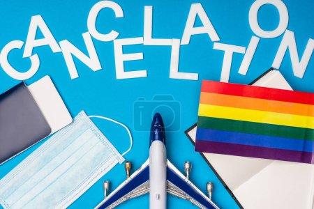 Photo pour Vue du dessus de l'avion jouet, passeport près du masque médical avec drapeau lgbt et l'annulation de lettrage sur fond bleu - image libre de droit