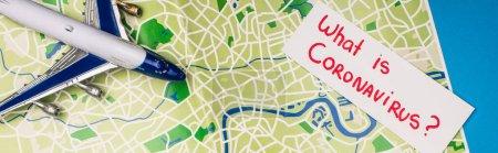 Photo pour Vue du dessus de la carte avec ce qui est lettrage coronavirus près de l'avion jouet sur la carte sur la surface bleue, vue panoramique - image libre de droit