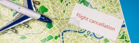 Photo for Top view of card with flight cancellation near toy plane on map isolated on blue, panoramic shot - Royalty Free Image