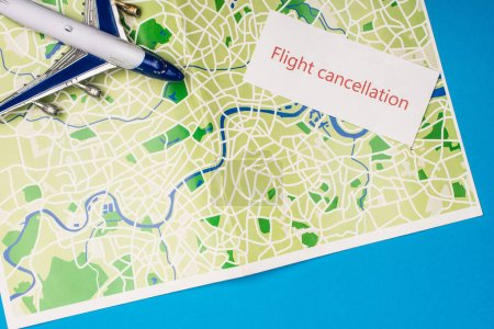 Top view of card with flight cancellation with toy plane on map isolated on blue