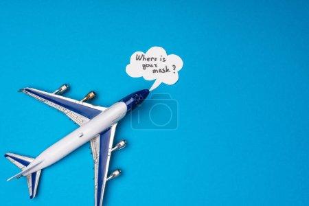 Photo pour Vue du dessus de l'avion jouet et bulle de parole avec où est votre masque lettrage sur la surface bleue - image libre de droit