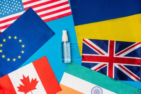 Photo for Top view of bottle of hand sanitizer near flags of countries on blue background - Royalty Free Image