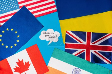 Top view of speech bubble with where is your mask lettering near flags of countries isolated on blue
