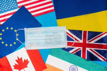 Photo for Top view of medical mask on flags of countries isolated on blue - Royalty Free Image