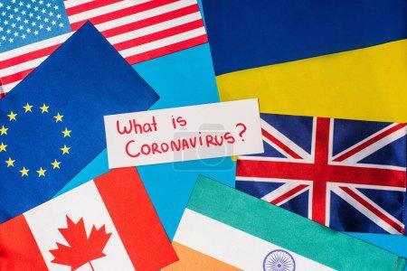 Photo pour Vue du dessus de la carte avec ce qui est lettrage coronavirus près des drapeaux des pays sur fond bleu - image libre de droit