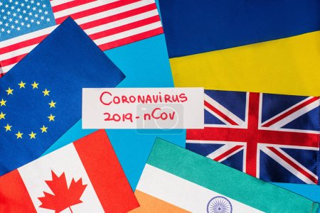 Photo for Top view of card with coronavirus 2019-nCov lettering near flags of countries on blue surface - Royalty Free Image