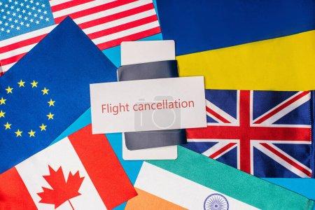 Photo pour Vue du dessus de la carte avec inscription d'annulation de vol sur le passeport avec billet d'avion et drapeaux des pays sur fond bleu - image libre de droit